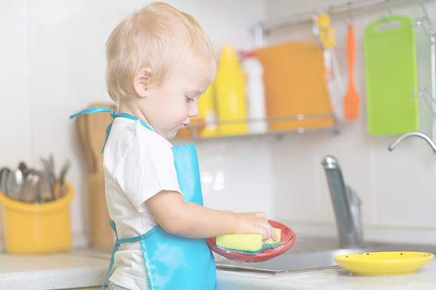 Preschool blonde boy cleaning dishes