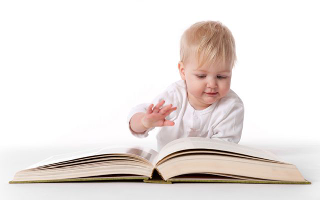 toddler reading a large book